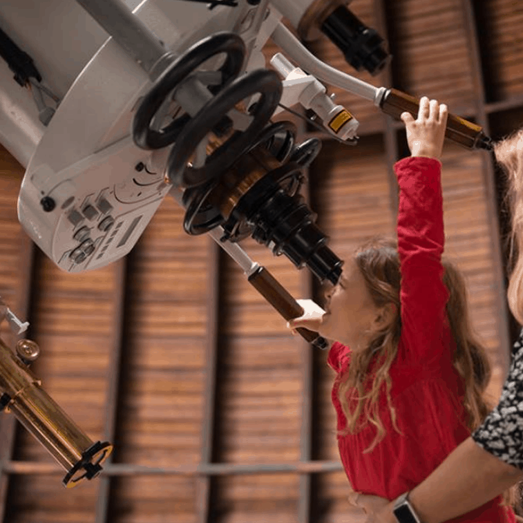 Mädchen blickt durch das Teleskop