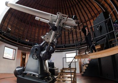 Demonstratorin blickt durch das Teleskop im Kuppelinneren
